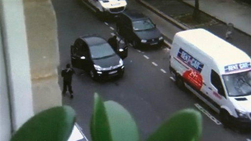 In this image from an amateur video recorded on January 7, 2015, masked gunmen get into a car moments after shooting a police officer outside the offices of French satirical newspaper Charlie Hebdo in Paris. (photo credit: AP/Jordi Mir)