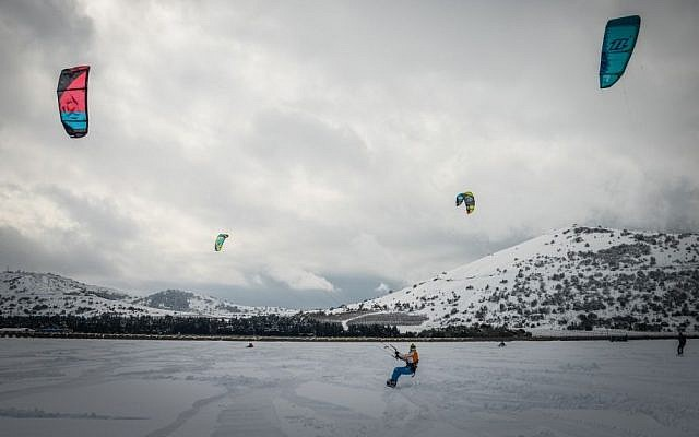 Israeli youths use kites to snowboard on a snow-covered field in the Golan Heights, January 8, 2015 (photo credit: Basal Awidat/Flash90)