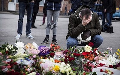 A man kneels next to flowers laid in honor of the shooting victims outside the Kruttoende cultural center in Copenhagen, Denmark on February 15, 2015. (photo credit: AFP PHOTO / CLAUS BJORN LARSEN)