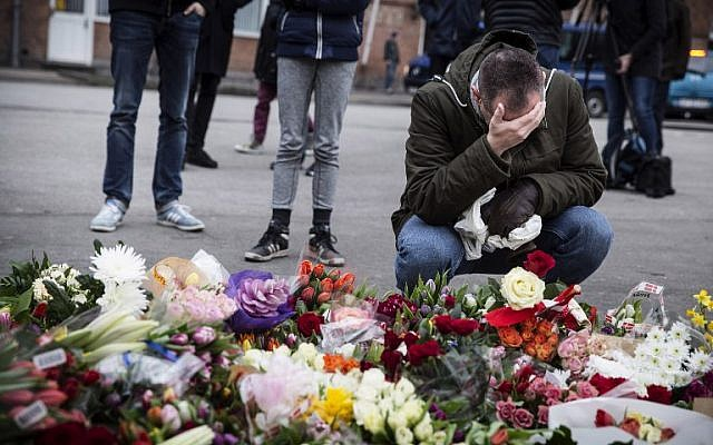 """A man kneels next to flowers laid in honor of the shooting victims outside the """"Kruttoende"""" cultural center in Copenhagen, Denmark on February 15, 2015. (photo credit: AFP PHOTO / CLAUS BJORN LARSEN)"""