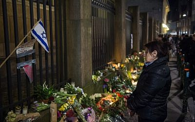 Well wishers reacts as they bring flowers and light candles to honor the shooting victims outside the main Synagogue in Copenhagen, Denmark on February 15, 2015 (photo credit: AFP/Odd Andersen)