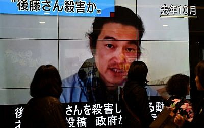 People walk past a big screen reporting that Kenji Goto was killed by the Islamic State in Tokyo on February 1, 2015. (photo credit: AFP PHOTO / Toru YAMANAKA)
