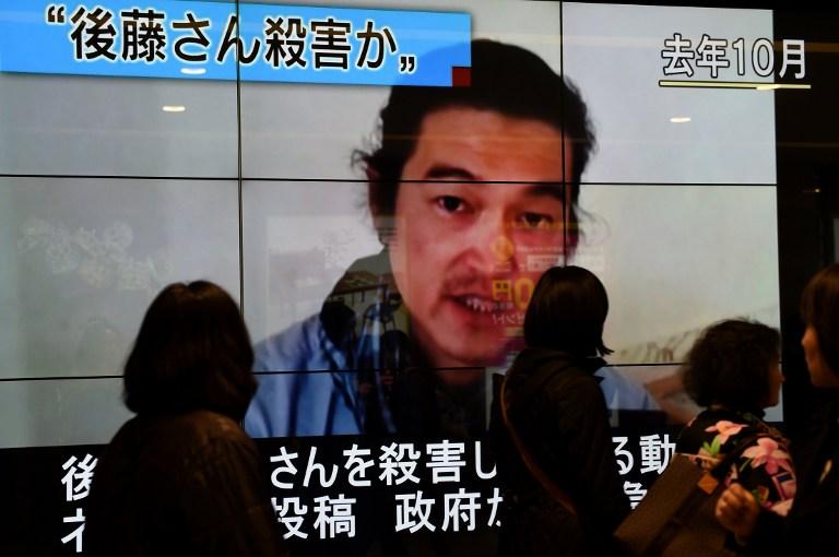People walk past a big screen reporting that Kenji Goto was killed by the Islamic State in Tokyo on February 1, 2015. (photo credit: AFP PHOTO / Toru YAMANAKA)