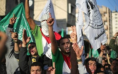 Palestinian men shout slogans during a rally near the Rafah border between southern Gaza Strip and Egypt on February 5, 2015 to condemn the decision of an Egyptian court to ban the armed wing of Hamas. (photo credit: AFP/Said Khatib)
