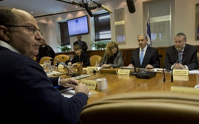 Israeli Prime Minister Benjamin Netanyahu sits in front of Defense Minister Moshe Yaalon, foreground, as he chairs the weekly cabinet meeting at his Jerusalem office on February 8, 2015. (photo credit: AFP/POOL/SEBASTIAN SCHEINER)