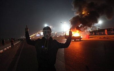 An Egyptian man wearing a mask of the Anonymous movement near a burning car outside a sports stadium in a Cairo's northeast district, on February 8, 2015, during clashes between supporters of Zamalek football club and security forces. (photo credit: AFP PHOTO / STR)