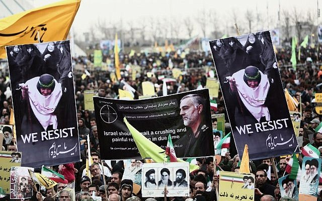 Iranian demonstrators hold a portrait of Iranian commander Major General Qassem Soleimani, the commander of the Qods Force and a central figure in the violent spread of Iran's revolution. Photo taken in Tehran's Azadi Square on Feb. 11, 2015 (Photo credit: Behrouz Mehri/AFP)