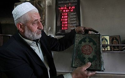 Palestinian Imam Ibrahim Abu Luha shows a burnt Koran, Islam's holy book, after a mosque was torched overnight in the West Bank village of al-Jaba, southwest of Bethlehem, February 25, 2015 .(photo credit: AFP/MUSA AL-SHAER)