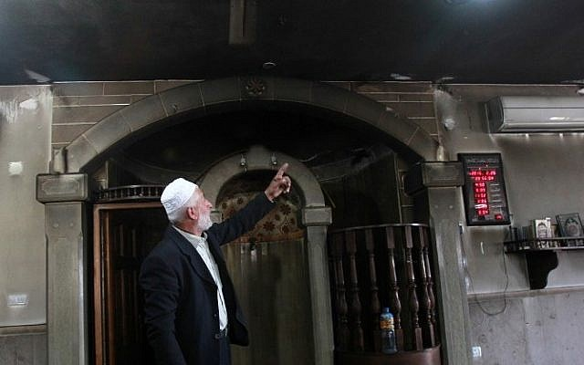 Palestinian Imam Ibrahim Abu Luha shows the damage at a mosque that was torched overnight in the West Bank village of al-Jaba, southwest of Bethlehem, February 25, 2015. (photo credit: AFP/MUSA AL-SHAER)