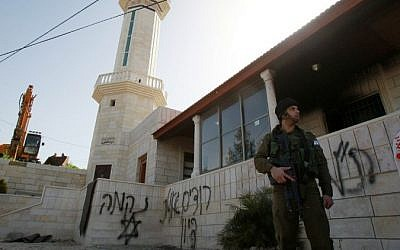 An Israeli soldier stands guard outside a mosque that was torched overnight with anti-Arab slogans in Hebrew sprayed on its walls, in the West Bank village of al-Jaba, southwest of Bethlehem, February 25, 2015. (photo credit: AFP/MUSA AL-SHAER)
