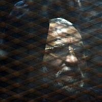 Egyptian Muslim Brotherhood leader Mohammed Badie stands behind bars during his trial in Cairo on February 28, 2015 (Mohamed el-Shahed)