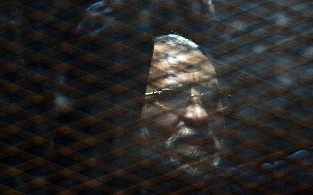Egyptian Muslim Brotherhood leader Mohammed Badie stands behind bars during his trial in Cairo on February 28, 2015 (Photo credit: Mohamed el-Shahed)