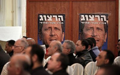 Israeli Arabs sit under a poster of Isaac Herzog, leader of the Zionist Union party, during an election campaign press conference in the northern Israeli-Arab town of Shfaram on February 28, 2015 (AFP PHOTO/AHMAD GHARABLI)