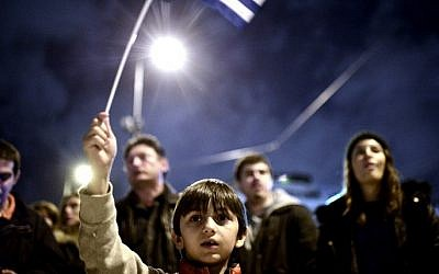 A young child waves the national flag as crowds gather in front of the Greek parliament in Athens on February 5, 2015 in support of the new anti-austerity government's efforts to renegotiate Greece's international loans (Photo credit: Louisa Gouliamaki/AFP)