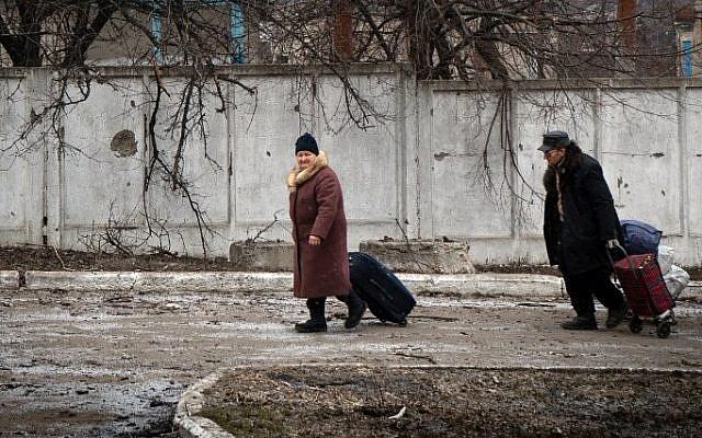 People walk with their belongings in the eastern Ukrainian town of Vuglegirsk in the Donetsk region,  February 7, 2015. (photo credit: AFP/ANDREY BORODULIN)