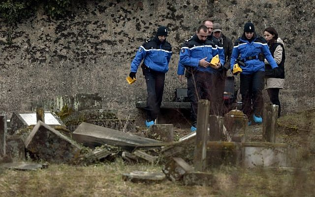 Illustrative: French gendarmes investigate in the area of defaced tombstones at the Jewish cemetery of Sarre-Union, northeastern France, on February 16, 2015. (AFP/Frederick Florin/ File)