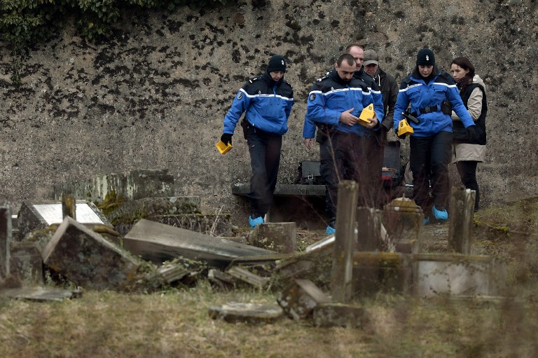 French Gendarmes investigate in the area of defaced tombstones at the Jewish cemetery of Sarre-Union, northeastern France, on February 16, 2015. (photo credit: AFP/Frederick Florin)