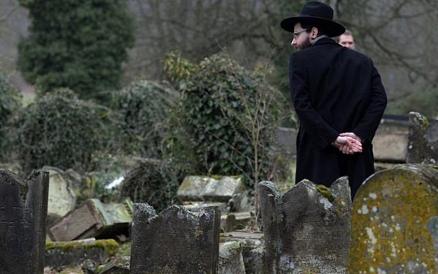 A member of the Jewish community looks at broken tombstones after a ceremony at the Jewish cemetery in Sarre-Union, eastern France, on February 17, 2015, following the desecration of around 300 tombs. (Photo credit: AFP/PATRICK HERTZOG)