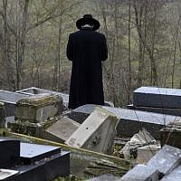 A member of the Jewish community looks at broken tombstones after a ceremony at the Jewish cemetery in Sarre-Union, eastern France, on February 17, 2015, following the desecration of around 300 tombs. (AFP/Patrick Hertzog)