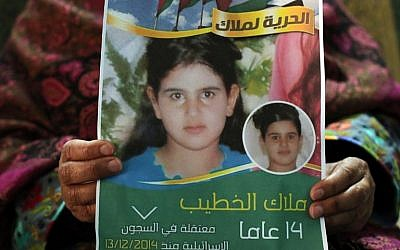 Khawla al-Khatib displays a poster on January 27, 2015, with a portrait of her 14-year-old daughter Malak, the youngest female Palestinian prisoner, whom Israel sentenced to two months in jail for trying to attack soldiers. (AFP/Abbas Moman)