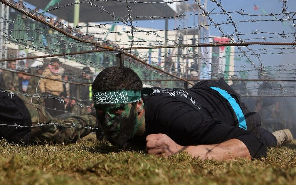 Illustrative photo of a Palestinian youth crawling under a barbed wire obstacle during a graduation ceremony for a training camp run by the Hamas movement on January 29, 2015 in Khan Yunis, in the southern Gaza Strip. (AFP photo/Said Khatib)