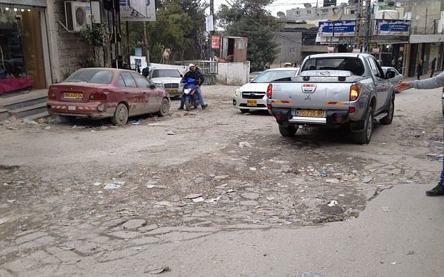 A deep pothole obstructs traffic on the main street of Shuafat Refugee Camp, a neighborhood of East Jerusalem located beyond the security barrier, January 26, 2015 (photo credit: Elhanan Miller/Times of Israel)