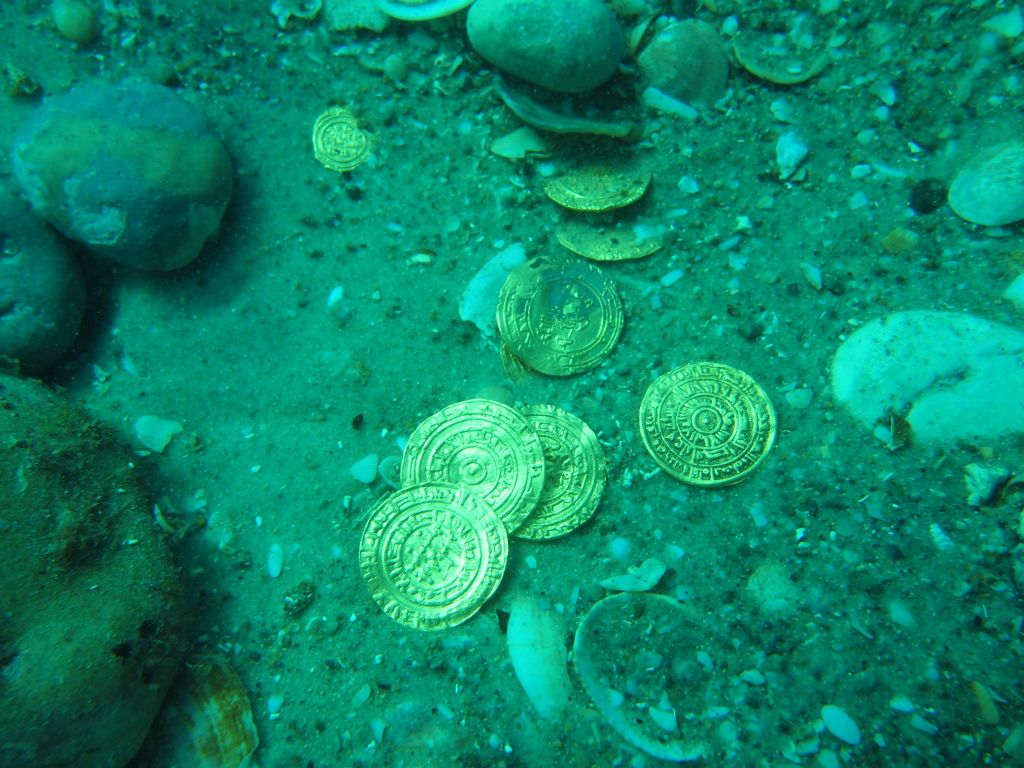 Islamic-era gold coins found off the coast of Caesarea by Israeli marine archaeologists (photo credit: Kobi Sharvit, courtesy of the Israel Antiquities Authority)