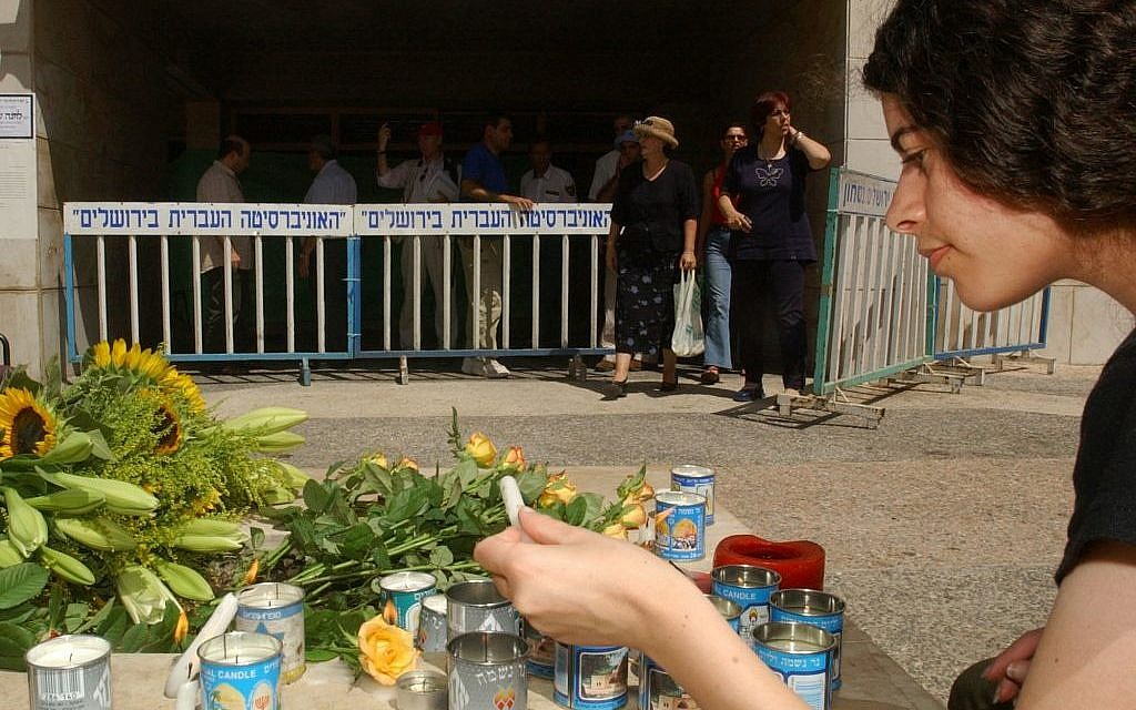 An unidentified Israeli woman lights candles at a memorial at the Hebrew University in Jerusalem Thursday August 1, 2002, a day after a bomb blew apart the university's Frank Sinatra International Students Center cafeteria, killing seven people, five of them Americans (AP Photo/Enric Marti)