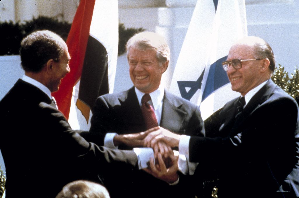 Egyptian President Anwar Sadat, US President Jimmy Carter, center, and Israeli Prime Minister Menachem Begin clasp hands on the north lawn of the White House as they sign the peace treaty between Egypt and Israel, March 26, 1979 photo credit: AP/Bob Daugherty