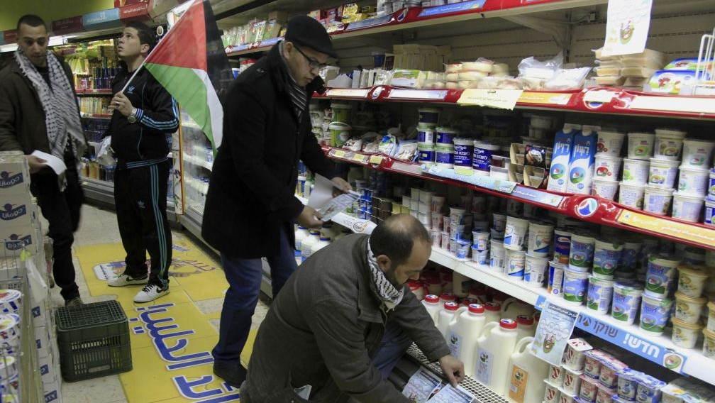 Illustrative: A Palestinian activist places a sign to boycott Israeli products at a supermarket in Bethlehem, West Bank,  February 11, 2015 (Mahmoud Illean/AP)