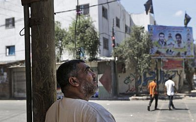 A Palestinian man watches the sky as Israeli forces' airplanes and drones fly over Gaza, in Beit Lahiya, northern Gaza Strip, Friday, July 25, 2014 (photo credit: AP/Lefteris Pitarakis)