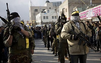 Palestinian gunmen of Fatah's al-Aqsa Martyrs' Brigades march during a military parade to mark the 50th anniversary of the Fatah movement in the Qalandia refugee camp near the West Bank city of Ramallah, Thursday, Jan. 1, 2015. (photo credit: AP Photo/Majdi Mohammed)