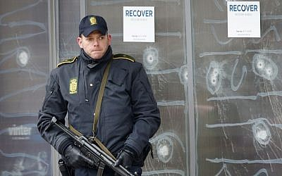 A police officer stands in front of the cultural center in Copenhagen, Denmark, on February 16, 2015, after a shooter killed one person. (photo credit: AP/Michael Probst)