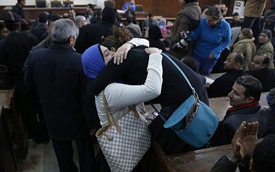 Jehane Rashed, left, wife of Al-Jazeera English defendant Baher Mohammed, cries as she celebrates with a friend in a courthouse near Tora prison in Cairo, Egypt, Thursday, Feb. 12, 2015. An Egyptian judge ordered Mohammed and another Al-Jazeera English journalist, Mohamed Fahmy, released on bail Thursday as their retrial on terror-related charges continues. (photo credit: AP Photo/Hassan Ammar)