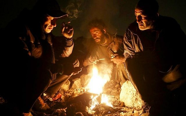 In this Wednesday, Feb. 11, 2015 photo, Drug addicts gather around fire to warm themselves, in a suburb of Tehran, Iran. (Photo credit: AP/Ebrahim Noroozi)