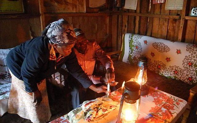Yosef Njogu and his wife Ruth prepare the candles before Shabbat in their home in Kasuku, Kenya. (Melanie Lidman/Times of Israel)