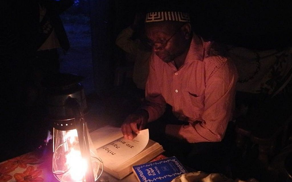 Yosef Njogu prepares for the Kabbalat Shabbat service in his home in the highlands of Kenya, where about 60 Kenyan Jews have a small and isolated community. (Melanie Lidman/Times of Israel)