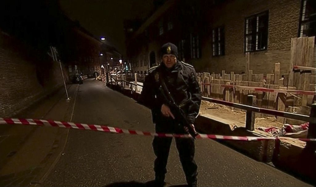 This image made from TV2 via Associated Press News video shows armed police guard behind police tape near a synagogue where police reported a shooting in downtown Copenhagen, Denmark, Sunday, Feb. 15, 2015. One person was shot in the head and two police officers were shot in the arms and legs, police said. (photo credit: AP Photo/TV2 via APTN)