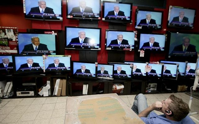A shopper stands in front of televisions broadcasting a speech by Prime Minister Benjamin Netanyahu at an electronics shop in Jerusalem. (Abir Sultan/Flash90)