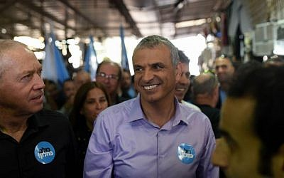 Kulanu party leader Moshe Kahlon walks with party members during a campaign stop at the Carmel market in Tel Aviv, February 4, 2015 (Ben Kelmer/FLASH90)