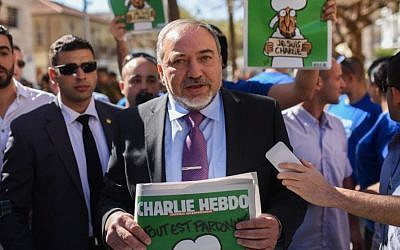 Foreign Minister and Yisrael Beytenu Chairman Avigdor Liberman holds an edition of the satirical weekly newspaper Charlie Hebdo during a protest in support of Charlie Hebdo in Tel Aviv on February 5, 2015 (photo credit: Ben Kelmer/Flash90)
