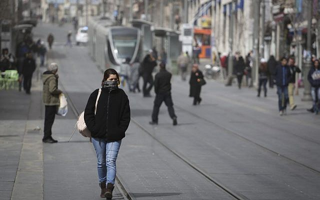 Israelis walk in Jerusalem as a dust storm hit the city on February 11, 2015. (Photo credit: Hadas Parush/Flash90)