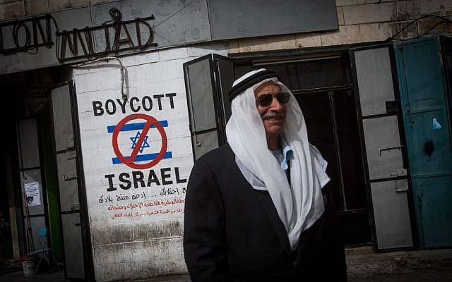 A Palestinian man walks by a grafitti sign calling to boycott Israel seen in the West Bank city of Bethlehem, February 11, 2015 (photo credit: Miriam Alster/Flash90)
