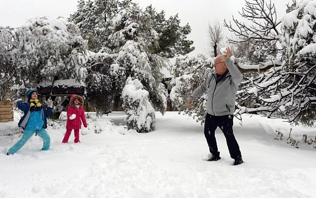 President Reuven Rivlin plays with his grandchildren in his snow-covered garden at the President's Residence in Jerusalem after a snow storm hit the capital, February 20, 2015 (Photo credit: Haim Zach/GPO)