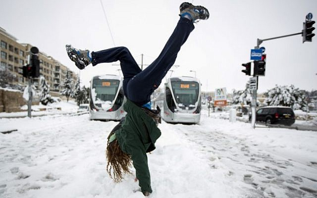 File: A young woman seen doing a hand stand on the lightrail tracks with the trains seen out of service behind her, on a snowy winter morning. February 20, 2015 (Photo credit: Muath Al Khatib/Flash90)