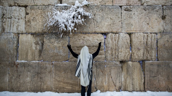 An ultra-Orthodox Jewish man prays at the Western Wall, in Jerusalem's Old City, on a snowy winter morning. February 20, 2015. (Photo credit: Yonatan Sindel/Flash90)