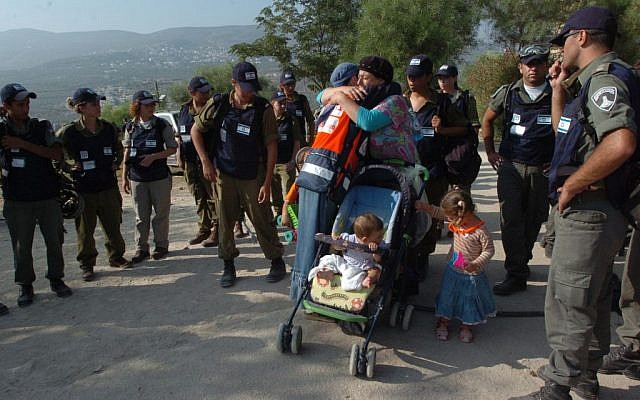 Two women hug before one leaves with her children from the settlement of Sa Nur in Samaria, as border police wait to evacuate her, August 23, 2005 photo credit: Nati Shohat/Flash90)