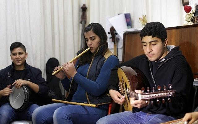 Palestinian musicians of al-Takht al-Sharqi (The Arab Orchestra) band take part in a rehearsal at the Edward Said National Conservatory of Music in Gaza City, on February 9, 2015. (photo credit: AFP/Mahmud Hams)