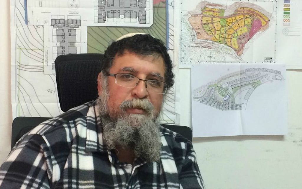 Netzer-Ariel executive director Arik Yefet sits in front of maps for the area where new homes are being built for the community's families. (photo credit: Renee Ghert-Zand/Times of Israel)