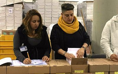 Central Elections Committee workers check voter registration lists, February 24, 2015. (photo credit: Renee Ghert-Zand/Times of Israel)
